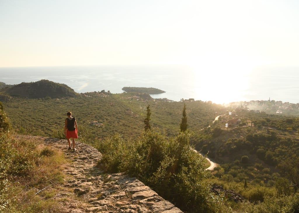 Frau läuft auf gepflastertem Weg über Olivenhainen und dem Meer