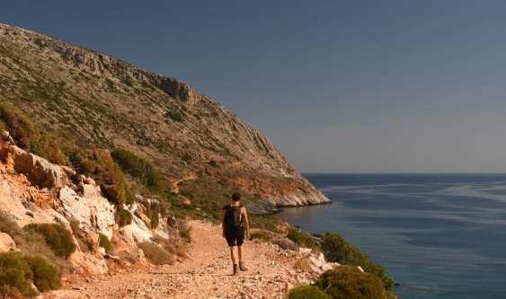 Frau wandert auf Schotterweg entlang Küste