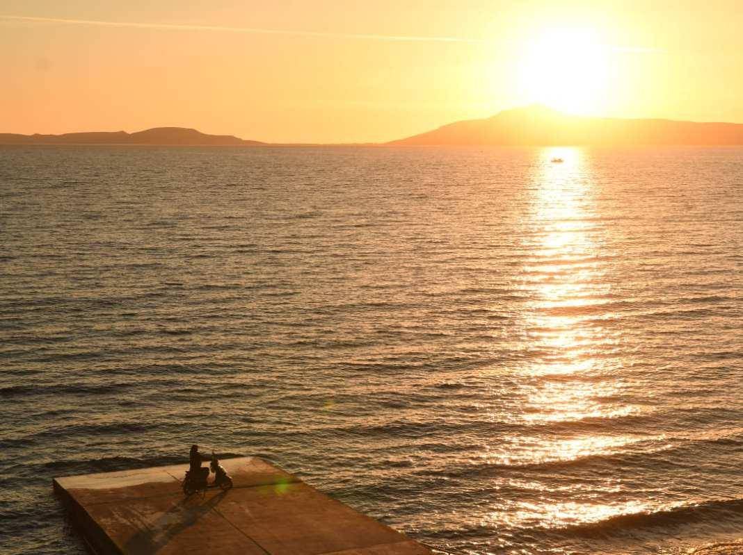 Mann mit Moped im Sonnenuntergang
