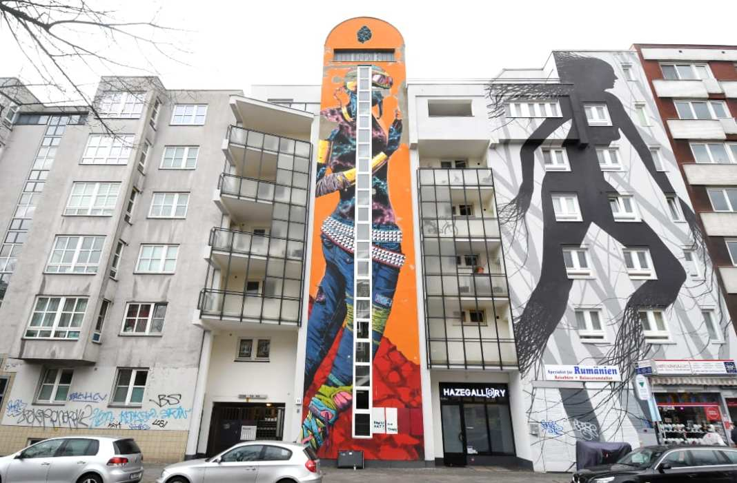 Zwei lange schmale Murals an Häuserwand
