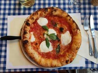 Napolitanische Pizza auf blau-weißer Tischdecke