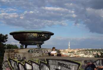 Junger Mann liegt neben Bronzeschale hoch über einer Stadt