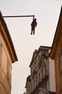 Skulptur eines Mannes baumelt an Stange in historischer Altstadt