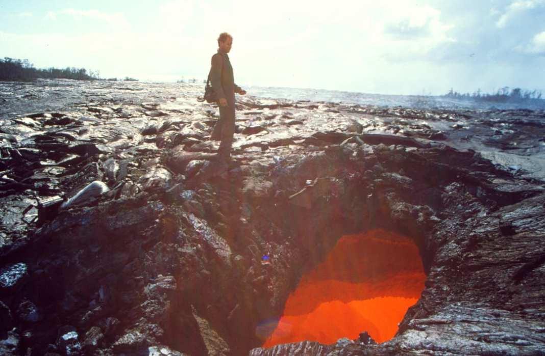 Mann neben Pool mit glühender Lava
