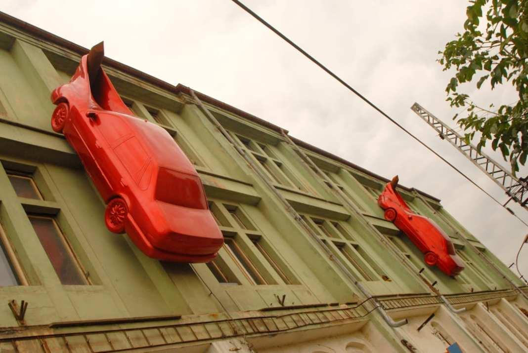 Zwei rote Autos hängen an Hauswand