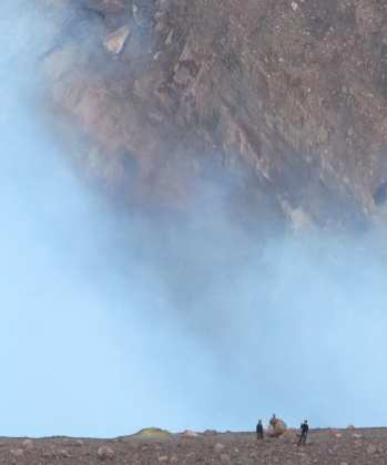 Winzige Menschen vor großem rauchenden Vulkankessel