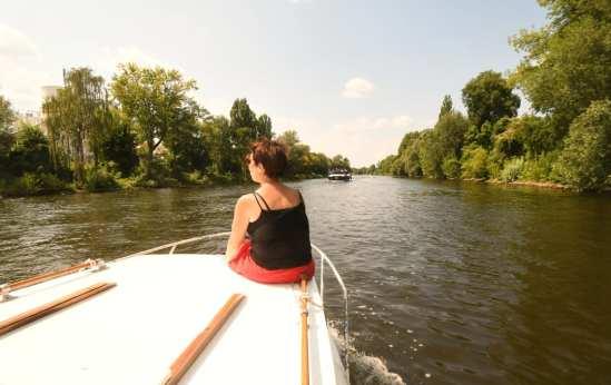 Frau sitzt auf einem Boot in einem Kanal