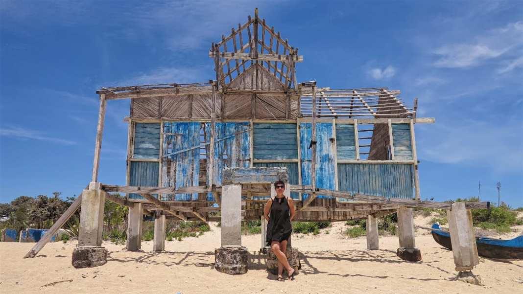 Frau steht vor Ruine eines Holzbaus am Strand