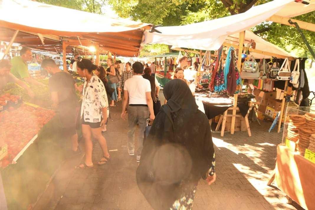 Frau mit schwarzem Tschador huscht über Markt
