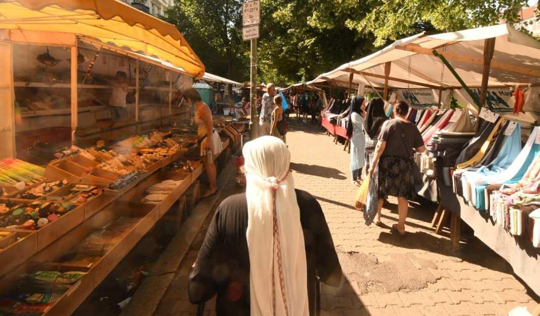 Frau mit Kopftuch läuft über Wochenmarkt