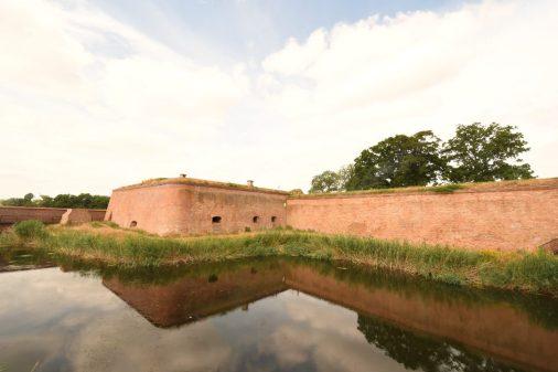 Backsteinmauer spiegelt sich in einem Fluss