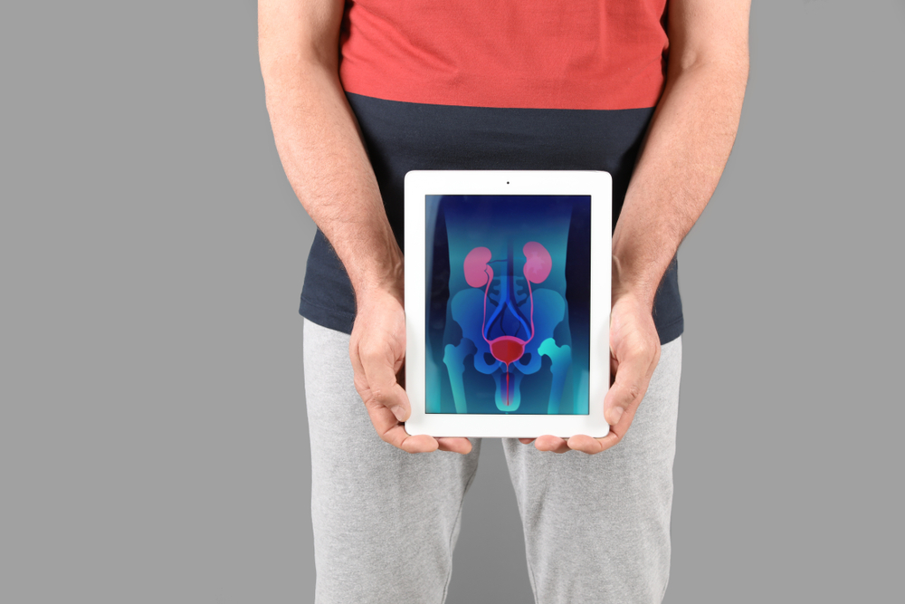man holding up tablet with images of prostate organs