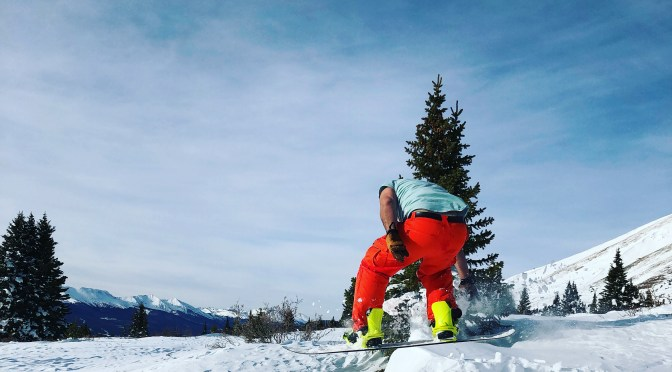 A person in bright red-orange snowpants and a turquoise t-shirt and gloves is strapped into neon green bindings on a snowboard as they fly over the snow after hitting a kicker with tall, deep green pine trees and a snowy mountain range in the background.