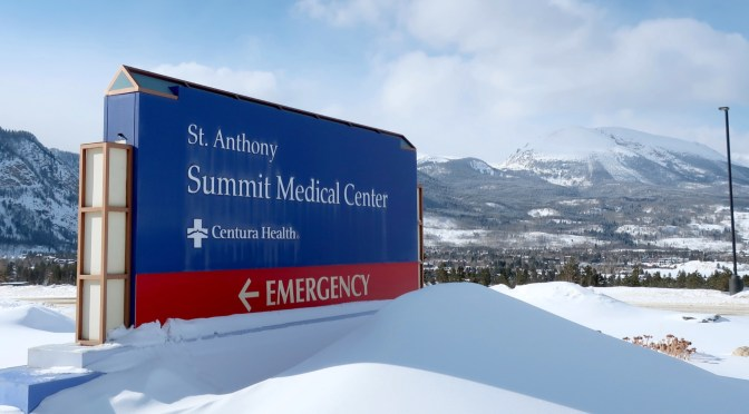 A blue sign reading St. Anthony Summit Medical Center, Centura Health, Emergency, with an arrow for direction to the emergency department, stands in front of Buffalo Mountain and the snowy Gore Range, with a smooth, soft-looking pile of fresh snow in the foreground.