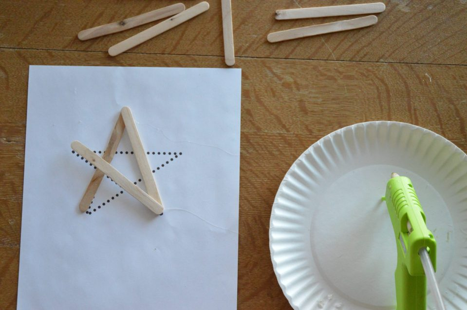 This picture shows the star template, glue gun, and where to place the glue sticks around the template.