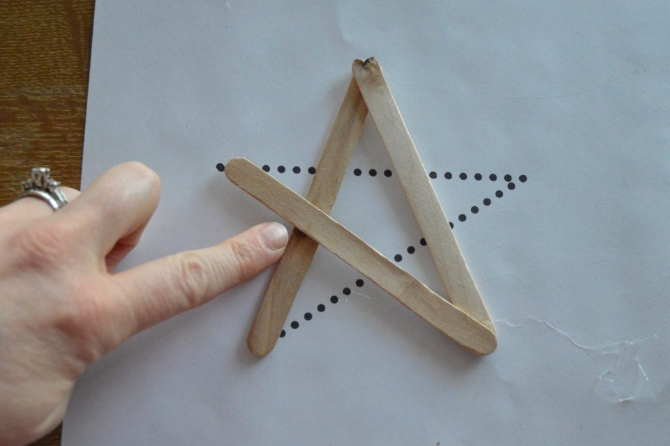 This shows where to place an extra glue dot to provide more stability to the star. The glue dot should be placed where the first and third popsicle sticks cross.