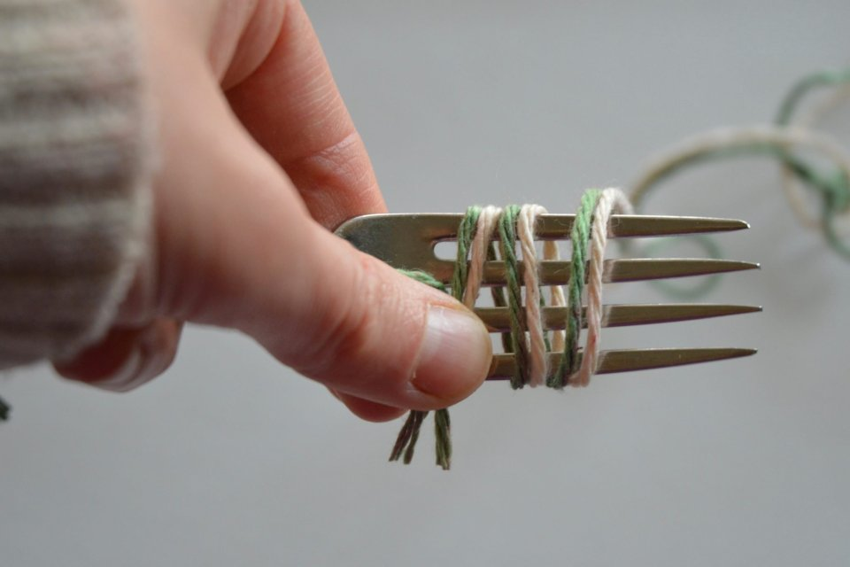 Hold the fork and yarn in your left yarn. Wrap the yarn around the fork to create the pom pom.