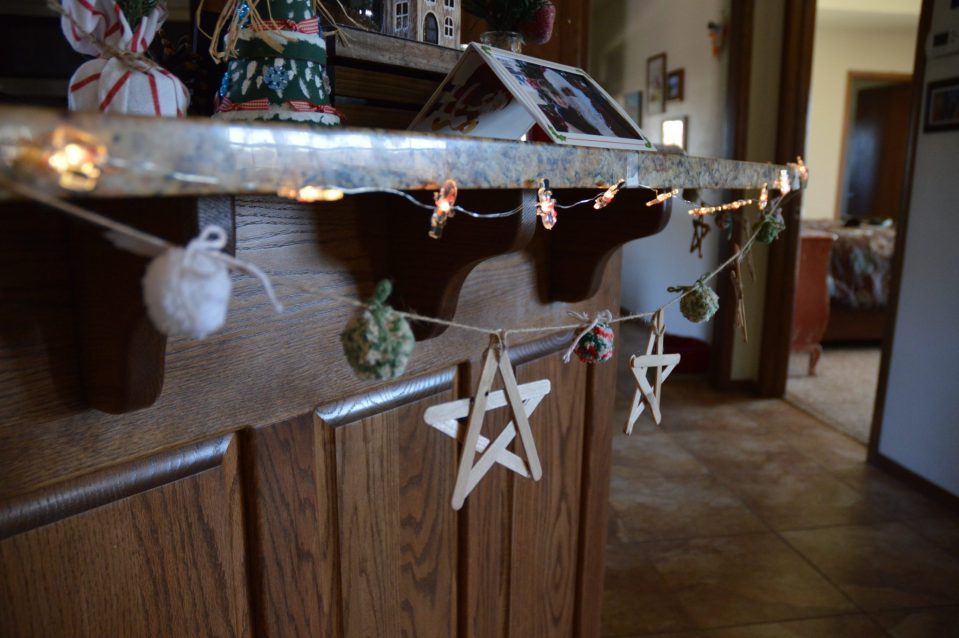 A yarn pom pom and wooden popsicle stick star garland hanging in the kitchen.