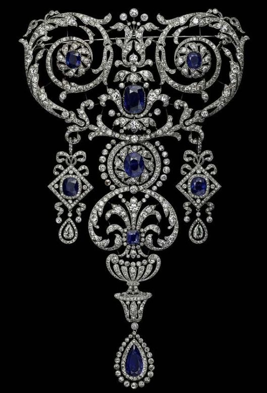 Devant de corsage, Cartier Paris, commande speciale de 1907, platine, diamants ronds taille ancienne et taille rose, un saphir de forme poire, sept saphirs de forme coussin (poids total des saphirs 51 carats environ), serti millegrain. Il est exceptionnel qu'une pièce de cette dimension (21x12,9cm) ait pu rester intact durant une centaine d'années, alors que les devants de corsage, tout comme les diadèmes, étaient dessertis ou transformes une fois passée de mode.