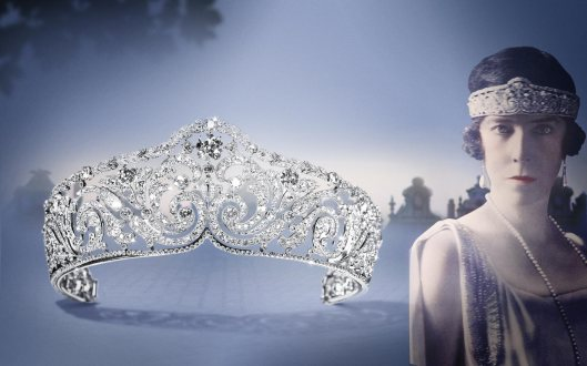 1910: This Scroll Tiara in platinum, composed of one cushion-shaped diamond and round old-cut diamonds, millegrain setting, was sold to Elizabeth, Queen of the Belgians in 1912.