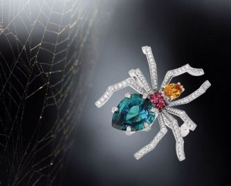 Chaumet spider ring in rhodium-plated 18k white gold, paved with diamonds, red spinels, a spessartite garnet and a central green tourmaline.