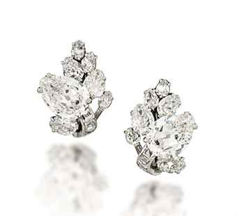 A PAIR OF MID-20TH CENTURY DIAMOND EAR CLIPS, BY CARTIER (estimate 60,000-80,000). Each modelled as a foliate spray, set with a principal old-cut pear shaped diamond weighing approximately 2.90 and 2.96 carats respectively, to a similarly-set diamond cluster surround, raised on a square-cut diamond stem, circa 1950, 2.2cm long.