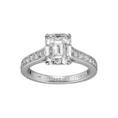 This solitaire has been a Cartier classic since 1895. The elegance of the lines is unique, the refined and light setting allows the light of the diamond to flow freely. Platinum 950‰ ring set with brilliant-cut diamonds, central emerald-cut diamond available from 1.00 to 5.00 ct and over.