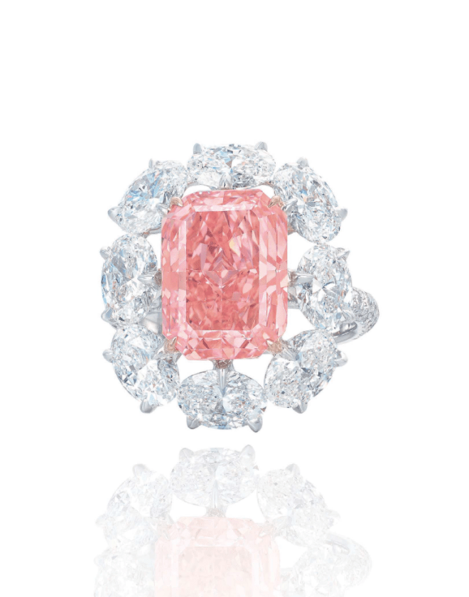 The Rectangular-cut Fancy Vivid Pink Diamond in an oval diamond surround, mounted in gold.