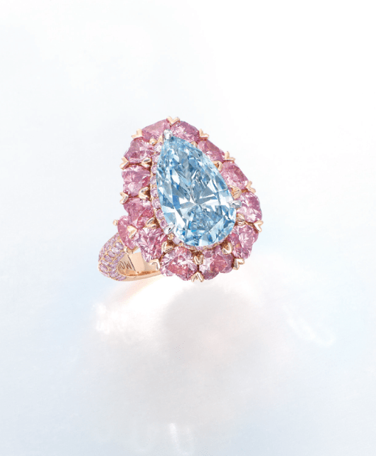 A rare coloured diamond ring by Moussaieff. Set with a pear-shaped fancy intense blue diamond weighing approximately 3.00 carats, within a brilliant-cut pink diamond frame and heart-shaped pink diamond surround, to the brilliant-cut pink diamond three quarter-hoop, mounted in 18k rose gold.