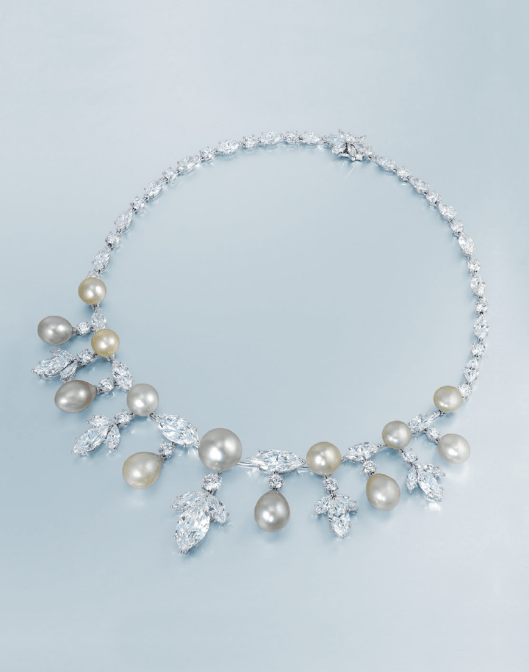 An elegant natural pearl and diamond necklace. The front designed as a series of natural white and cream button pearls measuring approximately 9.0 - 9.1 x 8.6 to 13.5 -13.6 x 10.9 mm, alternating with marquise-cut diamonds, suspending a fringe of white and cream natural pearl drops measuring approximately 8.8 - 8.9 x 11.7 to 11.1 - 11.2 x 15.0 mm and marquise-cut diamond trefoils, each joined by brilliant-cut diamonds, to the marquise and brilliant-cut diamond backchain and floral clasp, mounted in platinum and 18k white gold.