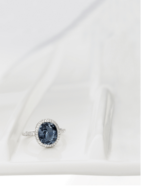 Set with an oval fancy deep blue diamond weighing 2.01 carats, amid a bombé frame pavé-set with brilliant-cut diamonds extending to the shank, mounted in platinum.