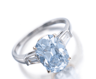 The cushion-shaped fancy intense blue diamond weighing 3.16 carats, set between tapered baguette diamonds.