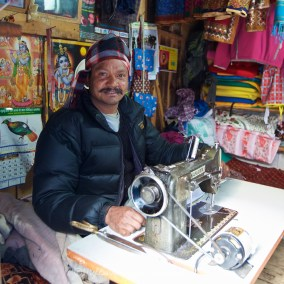 A tailor in his small shop at the side of the trail in Phakding