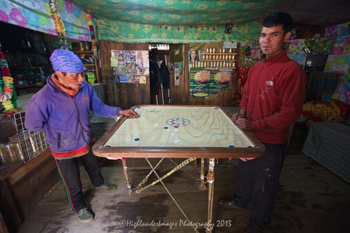 """This board game known as Carrom is very popular in Nepal and was seen being played in numerous small villages, like here between Phakding and Monjo. Carrom (also known as Karrom) is a """"strike and pocket"""" table game of Eastern origin similar to billiards and table shuffleboard. It is found throughout the East under different names though most non-eastern people know it by the East Asian name of Carroms (or Karrom). It is very popular in India, Pakistan, Bangladesh, Sri Lanka and surrounding areas. In the Indian sub-continent, many clubs and cafes have regular tournaments. Carrom is very commonly played within families and other functions. Different standards and rules exist in different areas."""