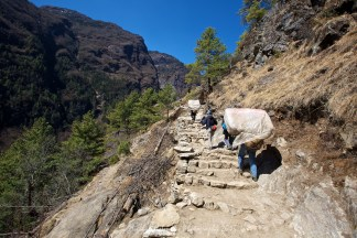 Full laden porters struggle up the steep rugged steps between Jorsalle and Namche Bazaar.