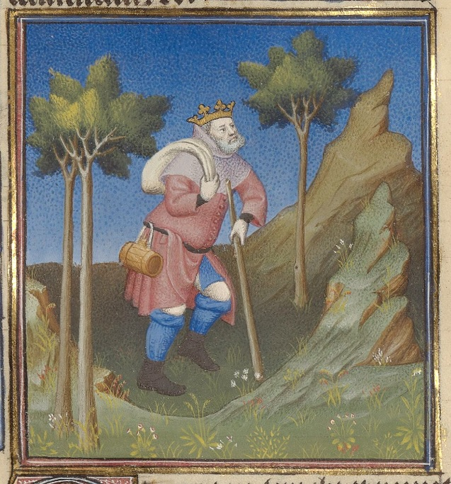 A man wearing a crown and in a pink tunic walks in the wilderness using a walking stick, while carrying a sack over his shoulder. He walks among trees.