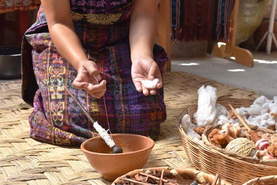 Rosario hand botanically dying cotton thread to be woven into fabric.