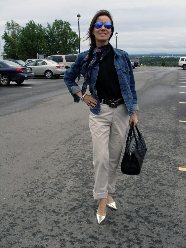 style book author in chinos, purple sunglasses, jean jacket, sweater, silver pumps