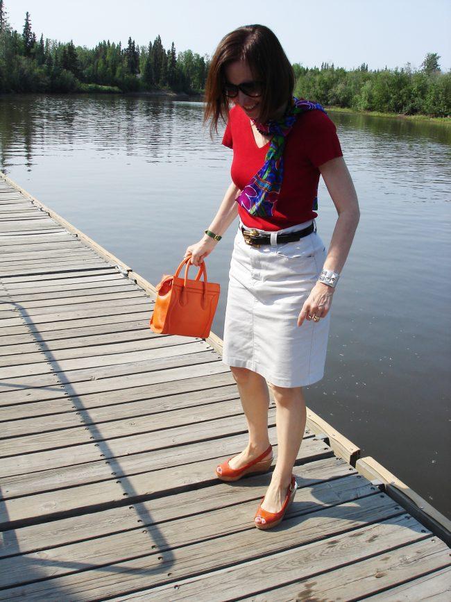 stylist in red sweater, cargoskirt, orange sandals with orange bag