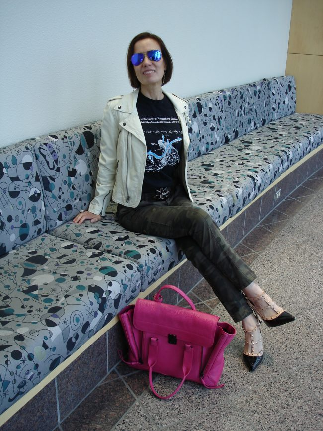 style book author in science inspired print top, white leather jacket, cargo pants, heels
