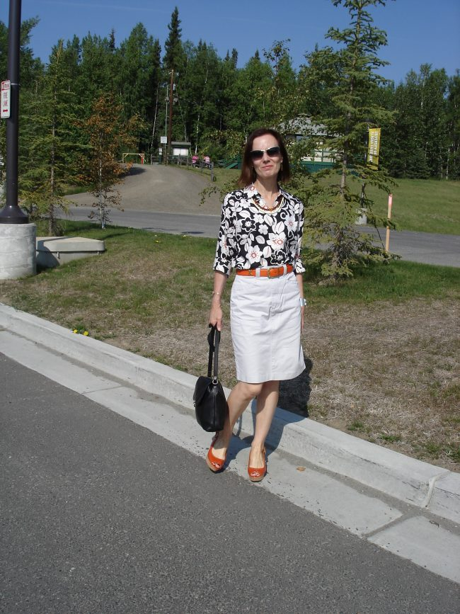 style book author in cargo skirt, tropical print blouse, orange accessories
