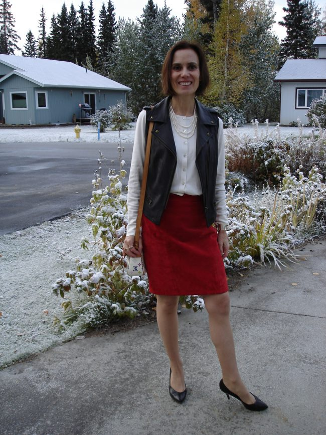 stylist in red suede skirt, black motorcycle vest, white top