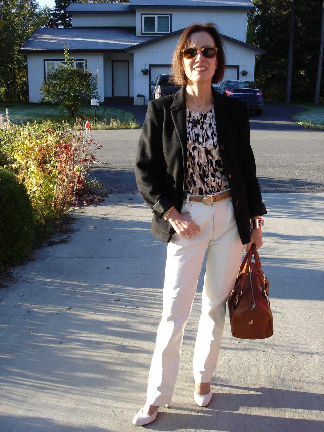 older woman in white leather pants, black blazer, tan bag