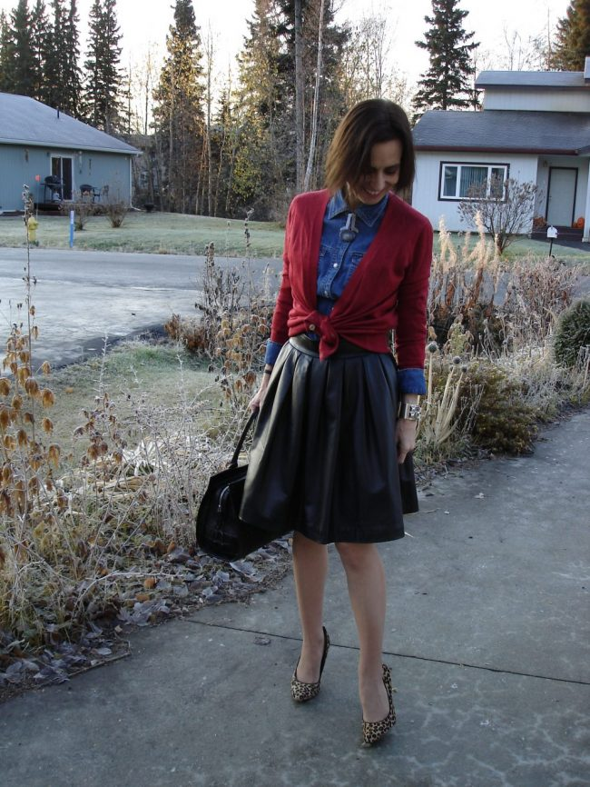 style book author in full leather skirt, jeans shirt, cardigan, heels