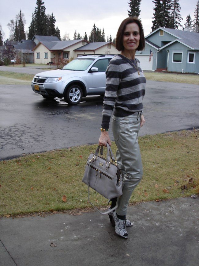 styleover40 woman wearing silver pants with a striped sweater