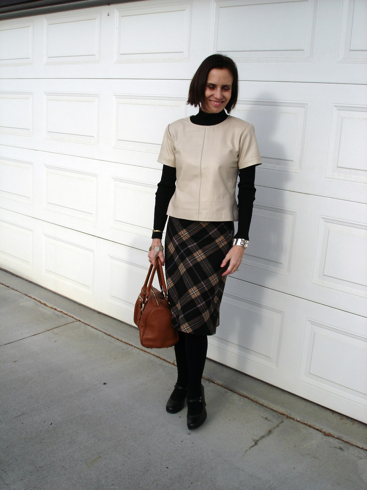stylist in cream leather shell, plaid skirt, Mary Janes, layering top carrying a satchel