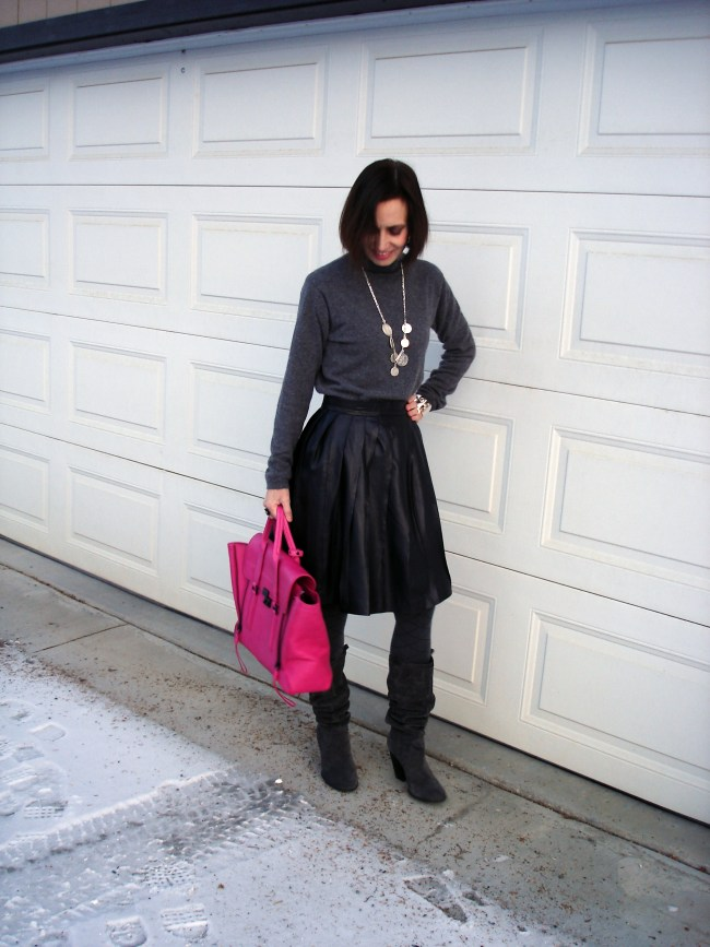#fashionover50 Woman wearing a turtleneck sweater with a pleated leather skirt
