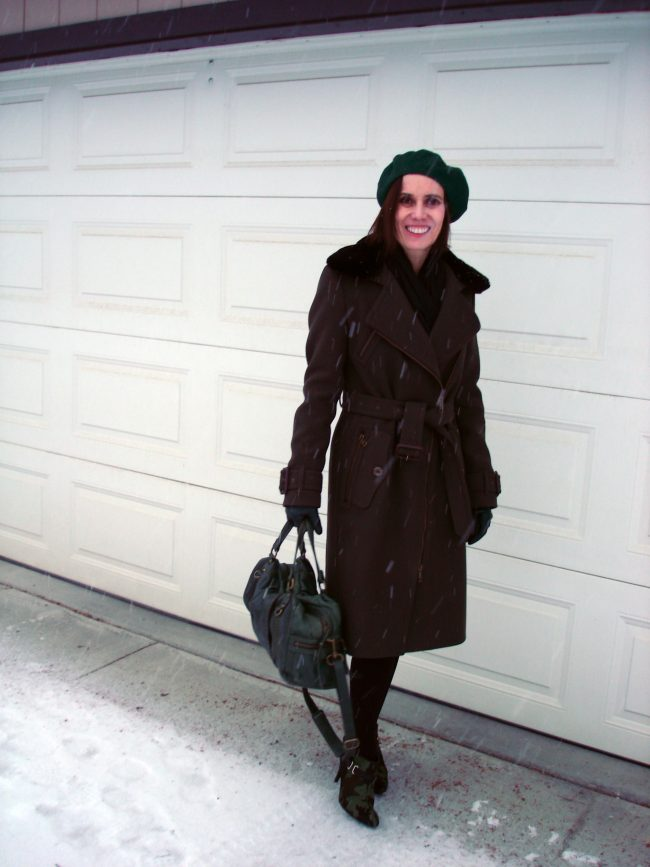 stylist in loden motorcycle midi coat with green beret and bag