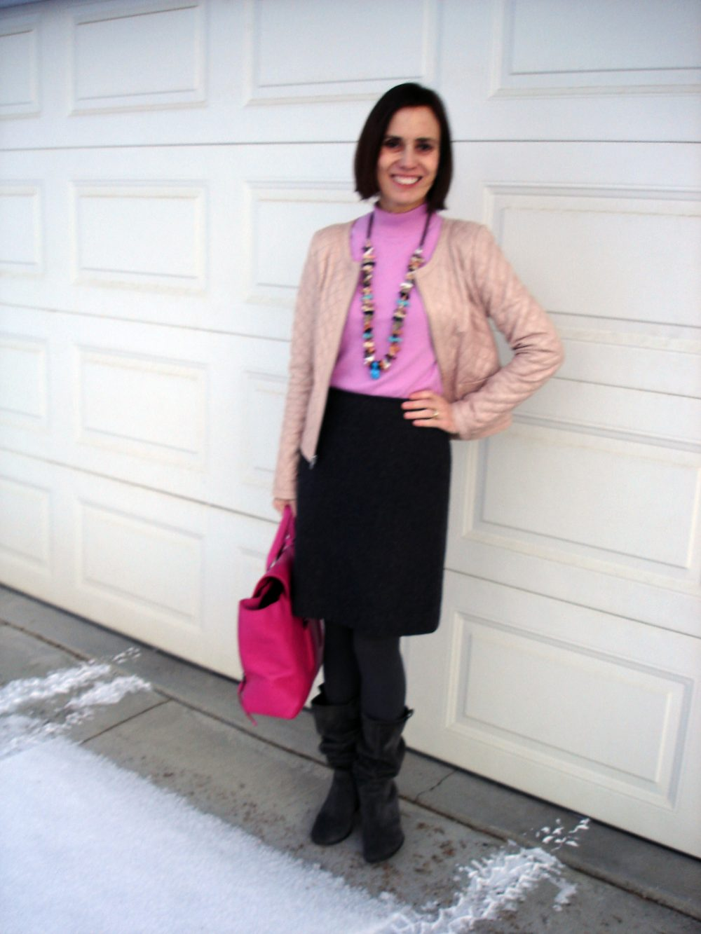 style book author in desatured gary-pink outfitof sweater, jacket, tights, skirt and boots
