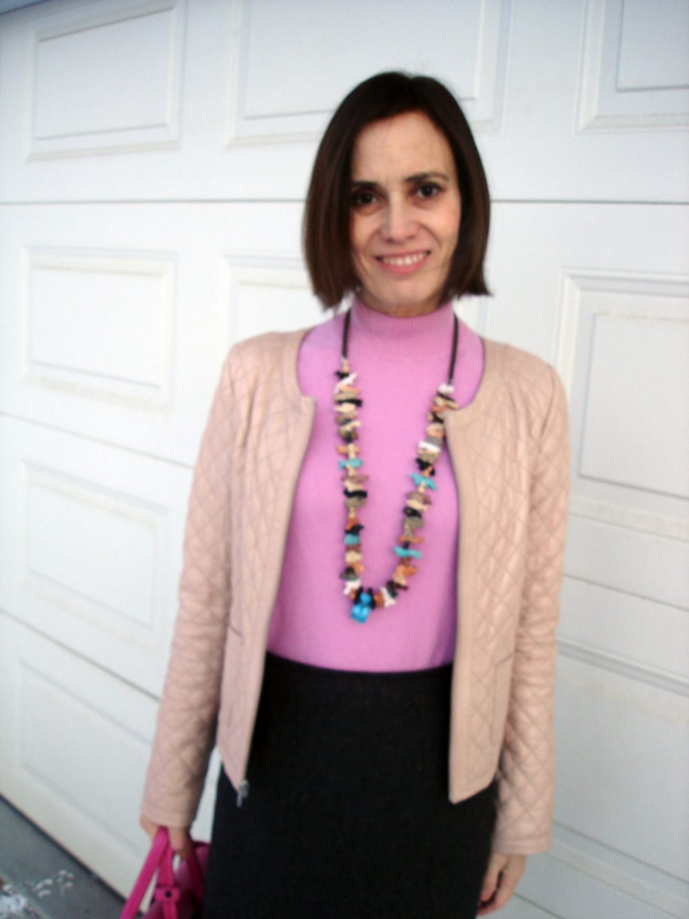 style influencer in pink sweater and blush jacket, gray skirt